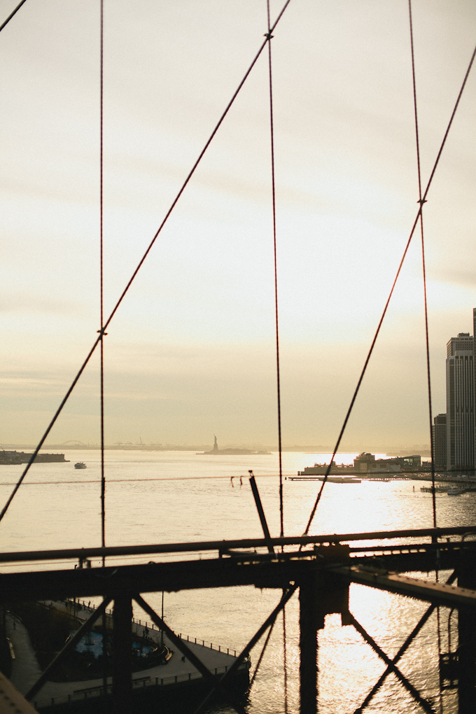 statue of liberty as seen from the brooklyn bridge near sunset